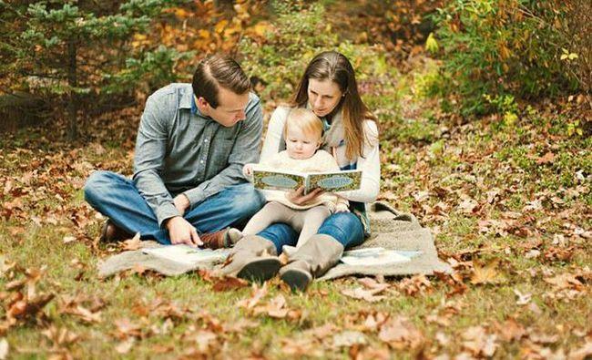 Сім`я читає в осінньому лісі