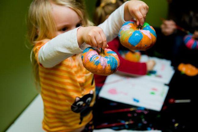Дівчинка розфарбовує гарбуз